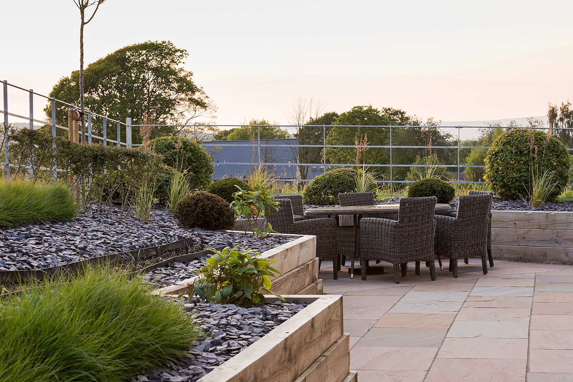 Rattan patio furniture. Contemporary Planting Scheme. Countryside views.